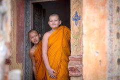 Two novices are looking in the temple of Buddhism in Thailand in Stock Photography
