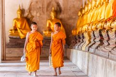 Two novices monk walking and talking in old temple at sunset time, Ayutthaya Province stock image