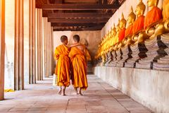 Two novices walking and talking in old temple at Ayutthaya Province. Thailand stock image