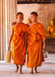 Two novices walking and talking in old temple at Ayutthaya Province stock photos