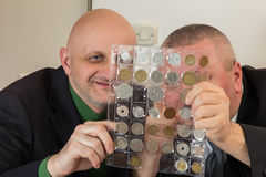 Two numismatists examines  collection of coin Royalty Free Stock Images