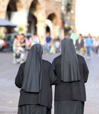 Two nuns with long dresses and a veil to cover the hair they wal. Two nuns with black long dresses and a veil to cover the hair they walk through the streets of royalty free stock photography