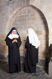 Two nuns in an old convent. Two young nuns passing eachother in a medieval convent (this is a composite, only 1 model release needed stock image