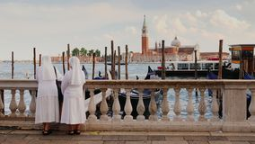 Two nuns in white robes admire the beautiful view of Venice and the bay with ships and gondolas. 4K video stock video footage
