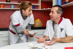 Two nurses talking about money Stock Images