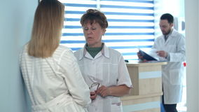 Two nurses talking near reception desk. Professional shot in 4K resolution. 097. You can use it e.g. in your commercial video, business, medicine, healthcare stock video