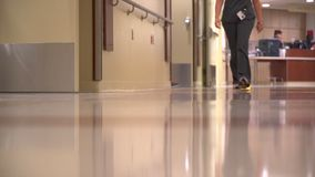 Two nurses walk down the hall in a modern hospital. A scene of two nurses walking down the hall in a modern hospital stock video footage