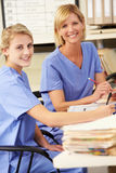 Two Nurses Working At Nurses Station Stock Photos