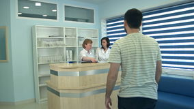 Two nurses working at reception desk greeting male patient. Professional shot in 4K resolution. 097. You can use it e.g. in your commercial video, business stock video footage