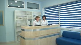 Two nurses working at reception desk greeting male patient stock photography