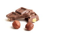 Two nuts and chocolate. Hazelnuts and chocolate pieces on white background Royalty Free Stock Photo