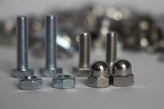 Two nuts and two deaf nuts. Cap nuts, four bolts on the back plate and a mountain of nuts and bolts royalty free stock photography