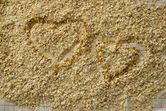 Two Oatmeal Hearts. Two hearts made with oatmeal, outlined with golden colored toasted oats. Background. Horizontal Stock Photography