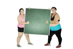 Two obese women with chalkboard on studio. Two obese women holding a blank chalkboard while showing thumbs up, isolated on white background Stock Images