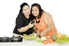 Two obese women cooking together with a smartphone. Picture of two obese women using a mobile phone while cooking together in the studio Royalty Free Stock Photography