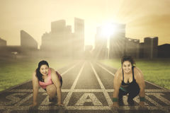 Two obese women ready to run. Portrait of two young obese women ready to run together on the start line, shot outdoors Stock Image