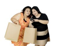 Two obese women shopping online with a smartphone. Picture of two obese women shopping online by using a smartphone, isolated on white background Stock Photography