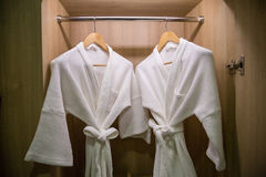Two off white color bathrobes hanging in warmly design closet, r. Oom for copy space stock photography