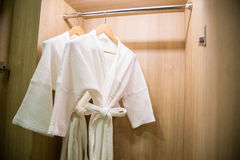 Two off white color bathrobes hanging in warmly design closet, r. Oom for copy space stock image