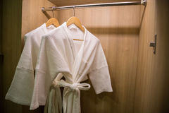 Two off white color bathrobes hanging in warmly design closet, r royalty free stock photography
