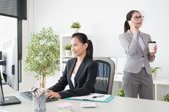 Two office lady take care of their own business stock images