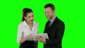 Two office worker look at a laptop together. Online shopping, Green screen stock video footage