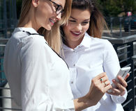 Two office worker looking at mobile phone. Stock Photography