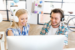 Two office workers at the desk with headphones Stock Photography