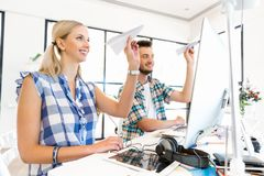 Two office workers at the desk playing with planes. Two young office workers playing with planes together at the desk Stock Images