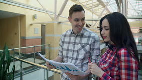 Two office workers discuss statistics documents inside. stock footage