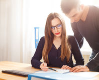 Two office workers discussing about papers at desk. Two office workers discussing about papers at the desk. Corporate business people looking at contract having Royalty Free Stock Photos