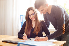 Two office workers discussing about papers at desk. Two office workers discussing about papers at the desk. Corporate business people looking through documents Royalty Free Stock Photo