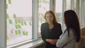 Two office workers discussing stickers pasted on window. Brunette in blue shirt with long hair talking to redhead woman in blue blouse, black jacket. Business stock video