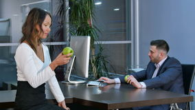 Two office workers having a break, aeting green apples and talking in office. Professional shot in 4K resolution. 085. You can use it e.g. in your commercial stock video
