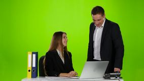 Two office workers laughing at what he saw on laptop stock footage