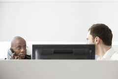 Two Office Workers Sitting In Office Cubicle Stock Photos