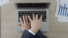 Two office workers typing on laptop actively, businessmen having fun at work. Stock footage stock footage