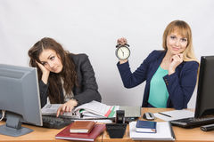 Two office workers wait for the end of the working day. Two young beautiful girls colleagues sitting at the same desk in the office Royalty Free Stock Photo