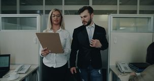 Two office workers walking from the office and speaking together looking through their documents.  stock video footage