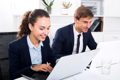 Two office workers work using laptops Stock Images