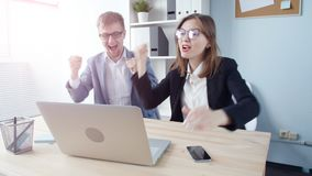 Two office workers. Young business people rejoice after a successful transaction. Young man and woman stock video footage