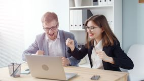Two office workers. Young business people rejoice after a successful transaction. Young man and woman stock video