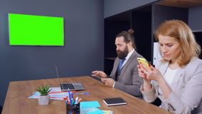 Two officeworkers get distracted from their phones on TV with green screen