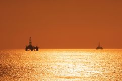 Two offshore oil rigs during s stock photos