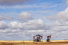 Two oil drills on farmland Royalty Free Stock Photo