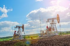 Two oil rigs in the field against the bright sun and blue sky with clouds royalty free stock image