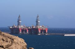 Two oil rigs moored to a dock in an industrial port royalty free stock photography