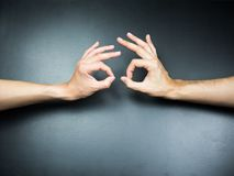 Two OK hands gestures to each other on black background.  Royalty Free Stock Photo