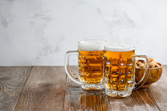 Two Oktoberfest beers with pistachio nuts on a wooden background. Two Oktoberfest beers with pistachio nuts on a wooden table Royalty Free Stock Photography