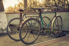 Two old bicycles at the village parking Stock Photos